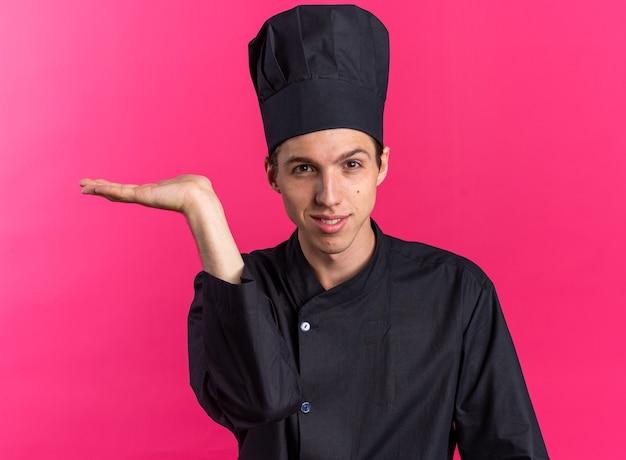 Blij jonge blonde mannelijke kok in uniform van de chef-kok en dop met lege hand