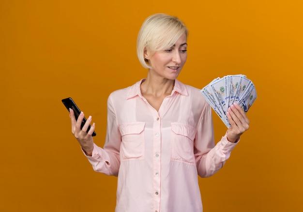 Blij jonge blonde slavische vrouw met telefoon en contant geld in haar hand kijken