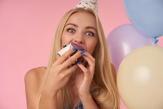 Blij jonge blonde vrouw vreugde tijdens het eten van verjaardagstaart, camera vreugdevol kijken met grote ogen geopend, genieten van leuk feest samen met vrienden, poseren op roze achtergrond