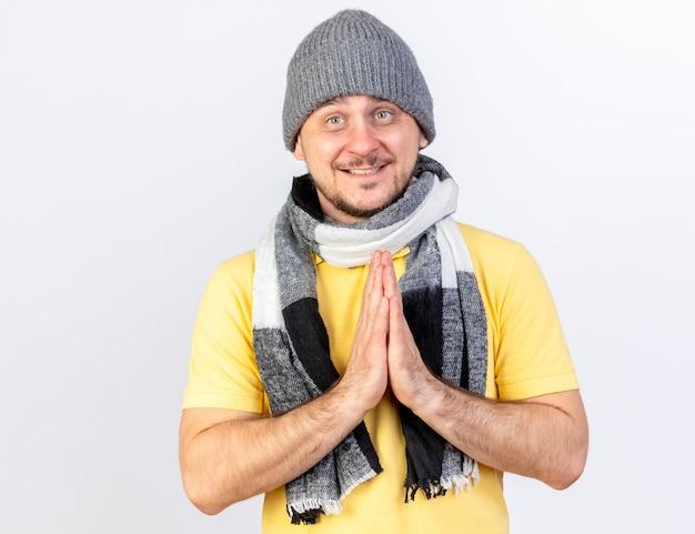 Blij jonge blonde zieke man met winter muts en sjaal houdt handen bij elkaar geïsoleerd op een witte muur