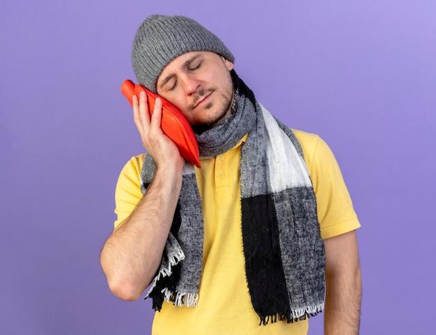 Blij jonge blonde zieke slavische man met muts en sjaal