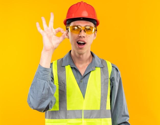 Blij jonge bouwer man in uniform dragen van een bril met goed gebaar geïsoleerd op gele muur