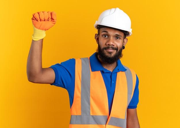 Blij jonge bouwer man in uniform met veiligheidshelm en handschoenen staan met opgeheven vuist geïsoleerd op oranje muur met kopieerruimte