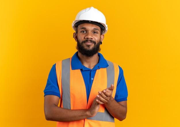 Blij jonge bouwer man in uniform met veiligheidshelm hand in hand samen geïsoleerd op oranje muur met kopie ruimte