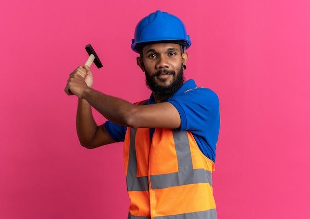 Blij jonge bouwer man in uniform met veiligheidshelm met hamer geïsoleerd op roze muur met kopie ruimte