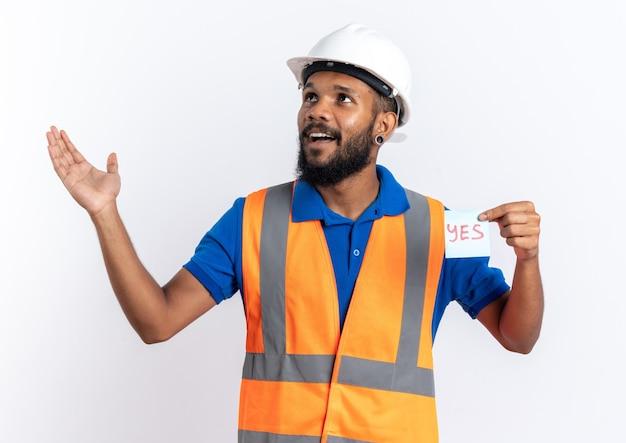 Blij jonge bouwer man in uniform met veiligheidshelm met ja notitie kijken naar kant geïsoleerd op een witte muur met kopie ruimte