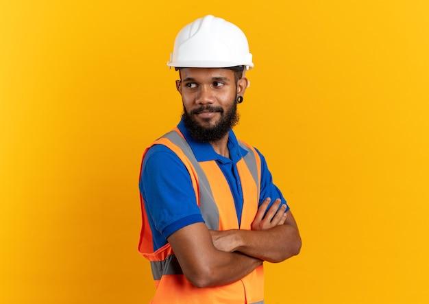 Blij jonge bouwer man in uniform met veiligheidshelm staande met gekruiste armen geïsoleerd op oranje muur met kopieerruimte