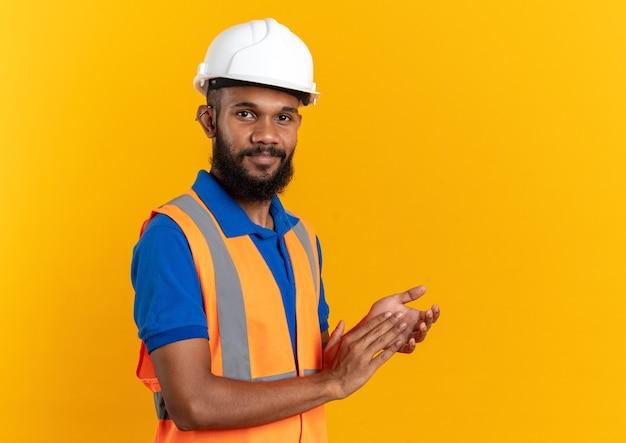 Blij jonge bouwer man in uniform met veiligheidshelm staande zijwaarts hand in hand samen geïsoleerd op oranje muur met kopie ruimte