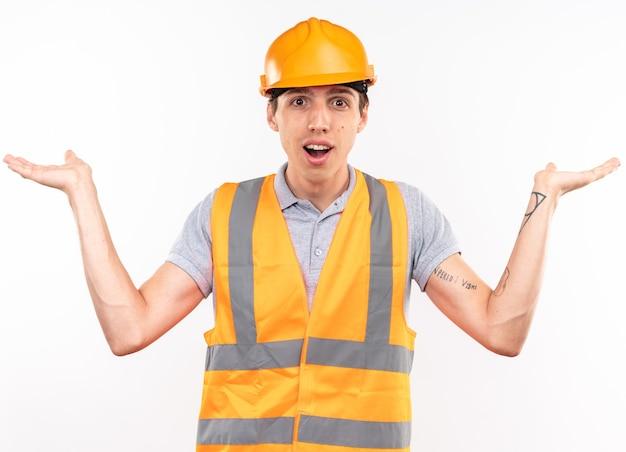 Blij jonge bouwer man in uniform spreidende handen geïsoleerd op een witte muur