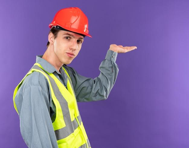 Blij jonge bouwer man in uniforme punten achter geïsoleerd op blauwe muur met kopie ruimte
