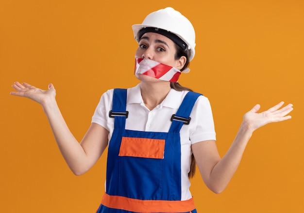 Blij jonge bouwersvrouw in uniform verzegelde mond met ducttape die handen uitspreidt die op oranje muur worden geïsoleerd