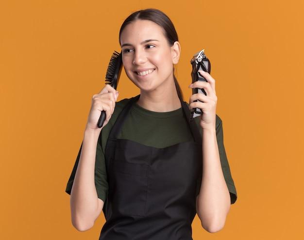 Blij jonge brunette kapper meisje in uniform houdt haartrimmer en kam kant kijken op oranje