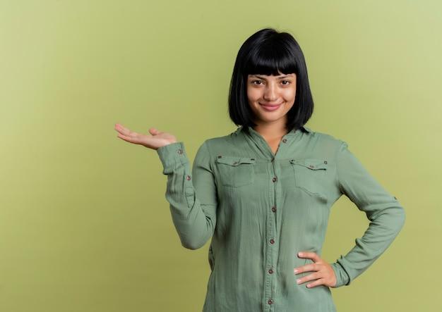 Blij jonge brunette kaukasisch meisje legt hand op taille en houdt hand open kijken naar camera geïsoleerd op olijfgroene achtergrond met kopie ruimte