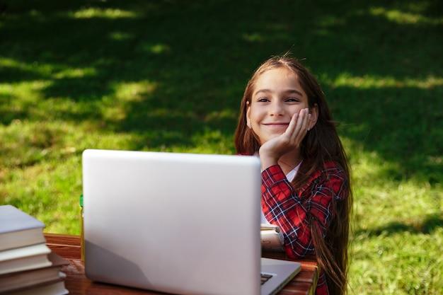 Blij jonge brunette meisje zitten bij de tafel met laptop