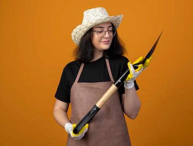 Blij jonge brunette vrouwelijke tuinman in optische bril en uniform dragen tuinieren hoed en handschoenen houdt en kijkt naar spade geïsoleerd op oranje muur