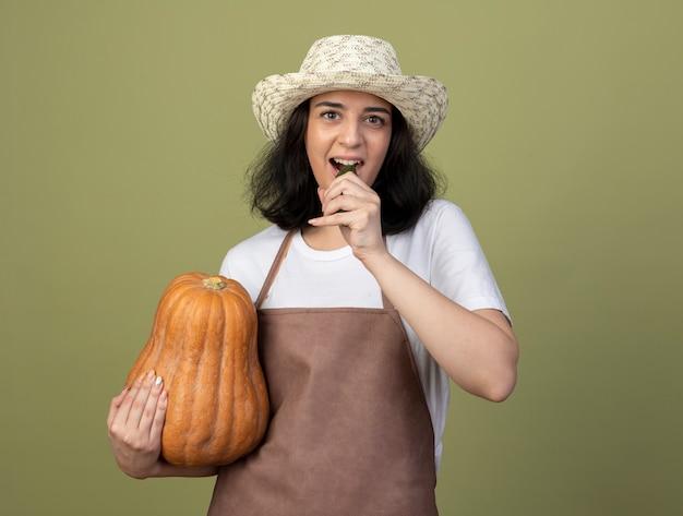 Blij jonge brunette vrouwelijke tuinman in uniform dragen tuinieren hoed houdt pompoen en doet alsof hij komkommer bijt geïsoleerd op olijfgroene muur