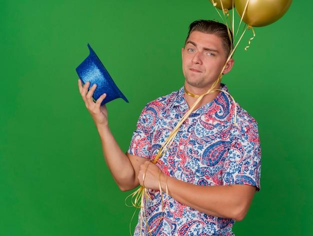 Blij jonge feest man met blauwe hoed en ballonnen gebonden rond nek geïsoleerd op een groene achtergrond