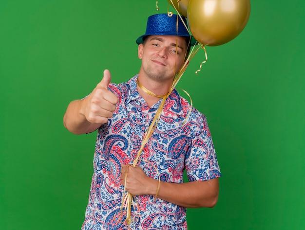 Blij jonge feest man met blauwe hoed met ballonnen vastgebonden rond de nek met duim omhoog geïsoleerd op groen