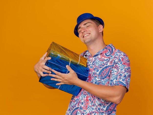 Blij jonge feest man met gesloten ogen dragen blauwe hoed omhelsde geschenkdozen geïsoleerd op oranje
