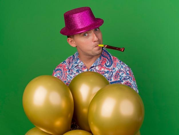 Blij jonge feest man met roze hoed staande achter ballonnen blazen partij ventilator geïsoleerd op groen