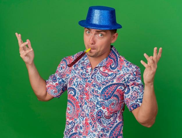 Blij jonge feestman met blauwe hoed blazende feestblazer en spreidende handen geïsoleerd op groen