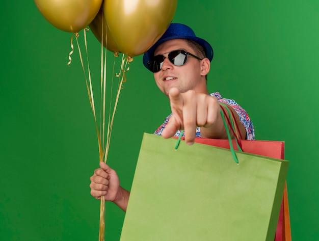 Blij jonge feestmens die blauwe hoed en bril draagt die ballonnen met geschenkzakken houdt die je gebaar tonen dat op groen wordt geïsoleerd