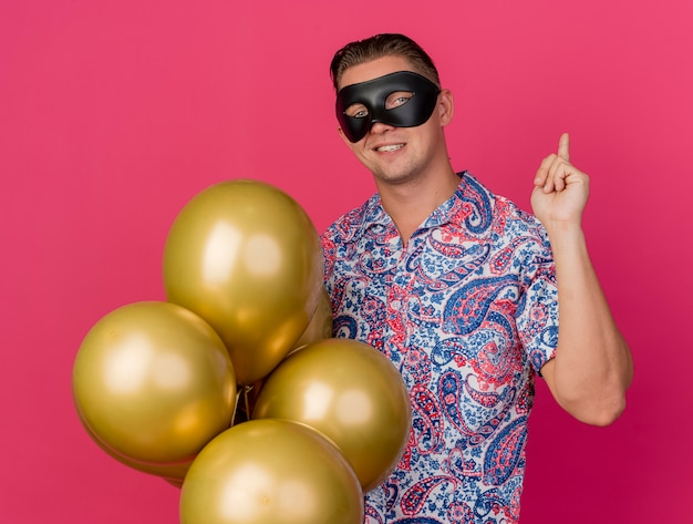 Blij jonge feestmens die maskerade oogmasker draagt met ballonnen en punten op de rug geïsoleerd op roze achtergrond
