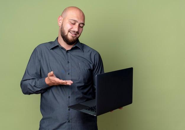 Blij jonge kale call center man bedrijf kijken en wijzend op laptop geïsoleerd op olijfgroene achtergrond met kopie ruimte