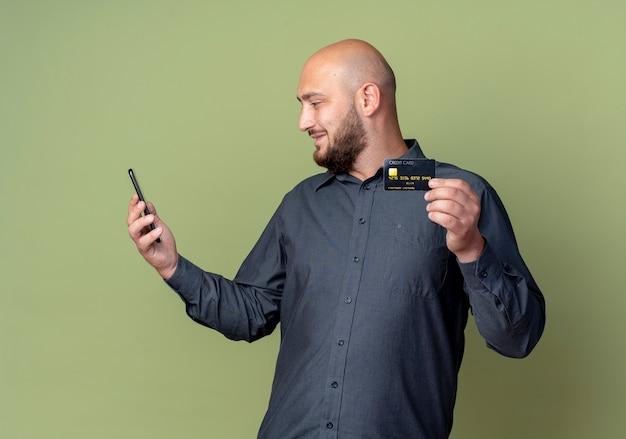 Blij jonge kale call center man houden en kijken naar mobiele telefoon met creditcard in een andere hand geïsoleerd op olijfgroene achtergrond