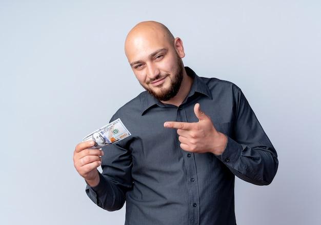 Blij jonge kale call center man houden en wijzend op geld geïsoleerd op een witte achtergrond