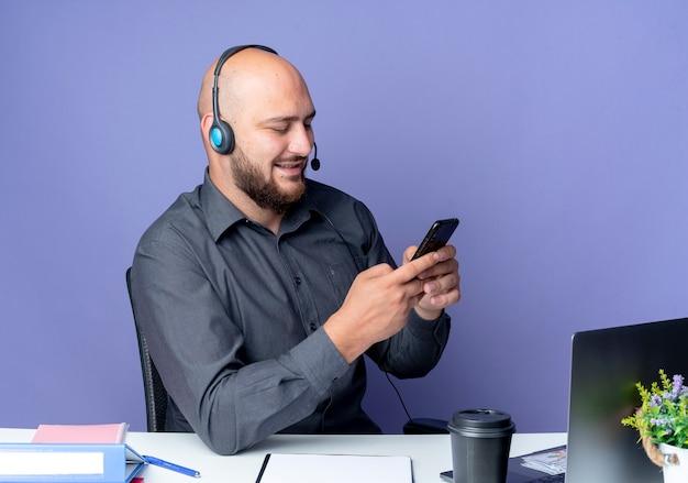 Blij jonge kale call center man met hoofdtelefoon zittend aan een bureau met uitrustingsstukken met behulp van zijn mobiele telefoon geïsoleerd op paarse achtergrond