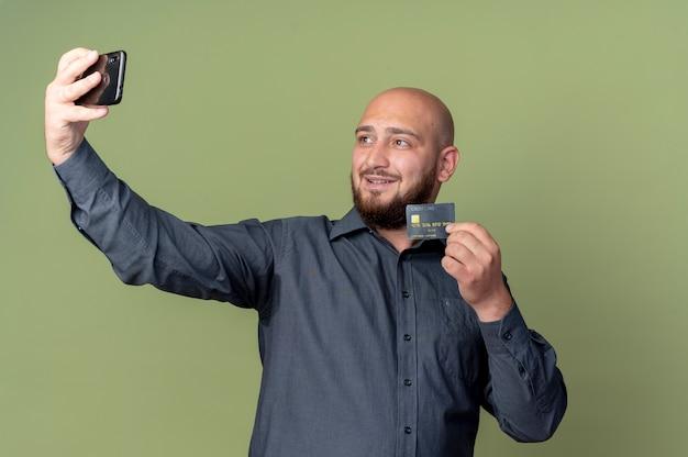 Blij jonge kale callcentermens die creditcard toont en selfie neemt die op olijfgroene achtergrond wordt geïsoleerd