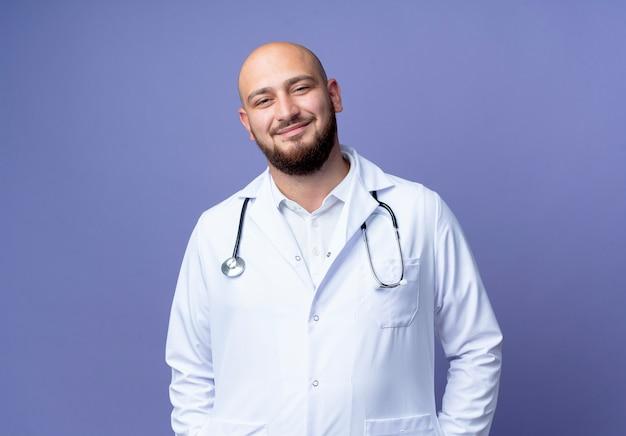 Blij jonge kale mannelijke arts die medische die mantel en stethoscoop draagt die op blauwe achtergrond wordt geïsoleerd