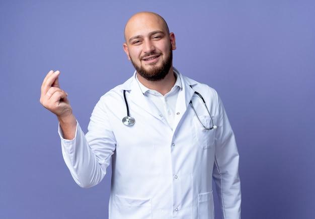 Blij jonge kale mannelijke arts die medische mantel en stethoscoop draagt die uiteindegebaar toont dat op blauwe achtergrond wordt geïsoleerd