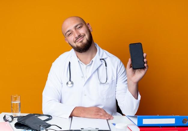 Blij jonge kale mannelijke arts die medische mantel en stethoscoop zit aan het bureau met medische hulpmiddelen die telefoon houden die op oranje achtergrond wordt geïsoleerd