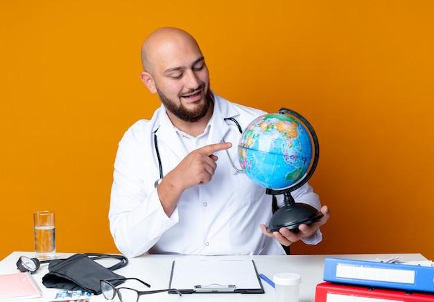 Blij jonge kale mannelijke arts dragen medische gewaad en stethoscoop zit aan bureau met medische hulpmiddelen houden en wijst op wereldbol geïsoleerd op een oranje achtergrond