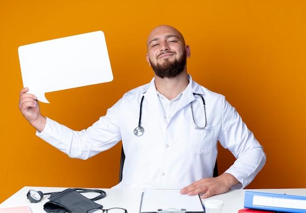 Blij jonge kale mannelijke arts dragen medische gewaad en stethoscoop zit aan bureau met medische hulpmiddelen houden praatjebel en zetten hand op heup geïsoleerd op een oranje achtergrond