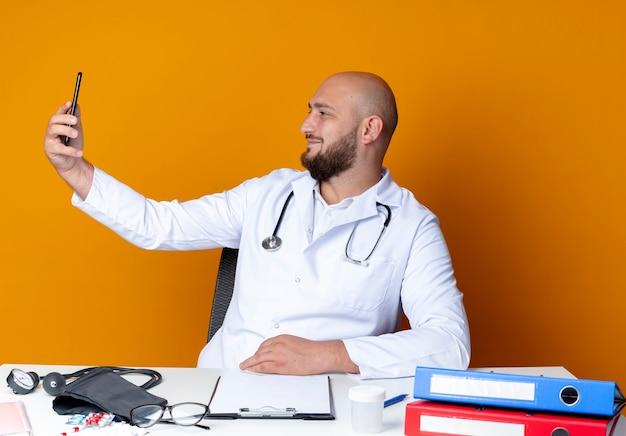 Blij jonge kale mannelijke arts dragen medische gewaad en stethoscoop zit aan bureau met medische hulpmiddelen nemen een selfie geïsoleerd op een oranje achtergrond