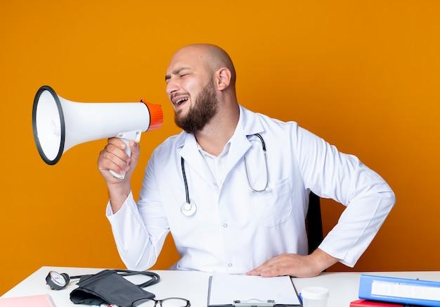 Blij jonge kale mannelijke arts dragen medische gewaad en stethoscoop zit aan bureau met medische hulpmiddelen spreekt op luidspreker geïsoleerd op een oranje achtergrond