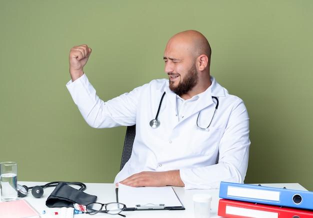 Blij jonge kale mannelijke arts dragen medische gewaad en stethoscoop zit aan bureau werken met medische hulpmiddelen doen sterk gebaar geïsoleerd op groene achtergrond