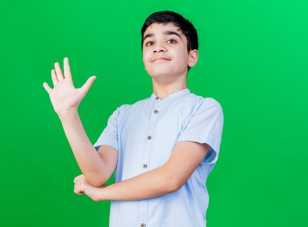 Blij jonge kaukasische jongen die camera bekijkt die hand onder elleboog houdt die vijf met hand toont die op groene achtergrond met exemplaarruimte wordt geïsoleerd