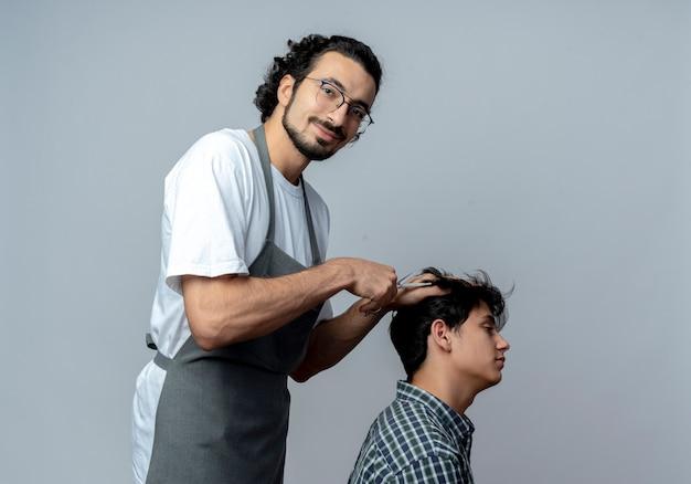Blij jonge kaukasische mannelijke kapper bril en golvende haarband dragen uniform staande in profiel te bekijken doen kapsel voor zijn jonge cliënt geïsoleerd op een witte achtergrond met kopie ruimte
