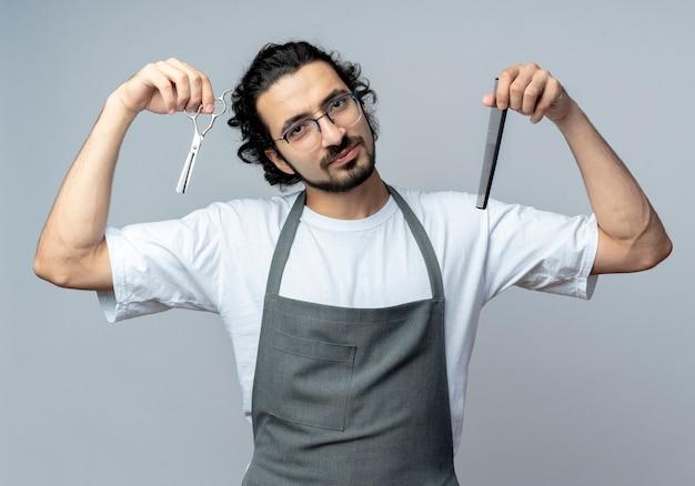 Blij jonge kaukasische mannelijke kapper die glazen en golvende haarband in eenvormige holdingskam en schaar draagt die op witte achtergrond wordt geïsoleerd