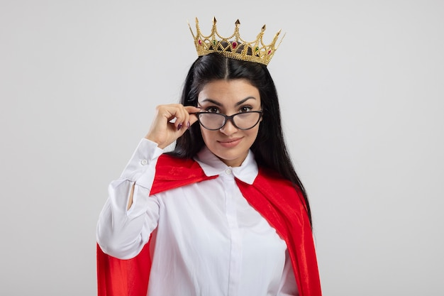 Blij jonge kaukasische superheld meisje bril en kroon grijpen bril kijken camera geïsoleerd op een witte achtergrond met kopie ruimte