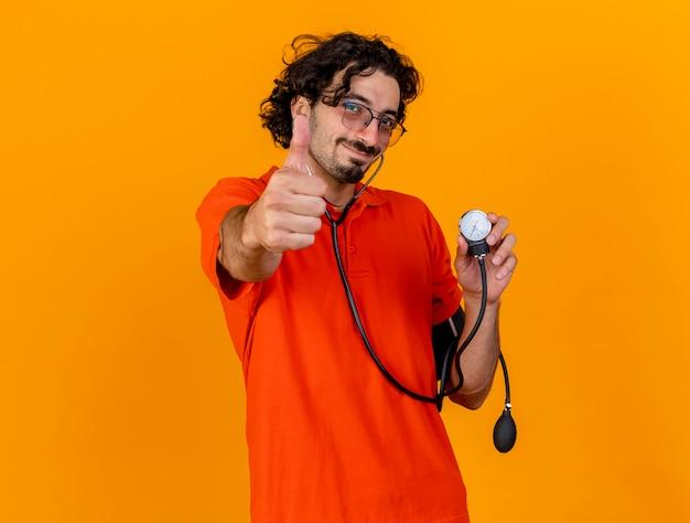 Blij jonge kaukasische zieke man met bril en stethoscoop houden bloeddrukmeter kijken camera weergegeven: duim omhoog geïsoleerd op een oranje achtergrond met kopie ruimte