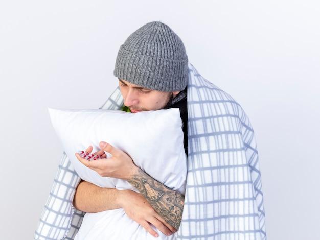Blij jonge kaukasische zieke man met winter hoed verpakt in plaid houdt pack van medische capsules en knuffels kussen geïsoleerd op een witte achtergrond met kopie ruimte