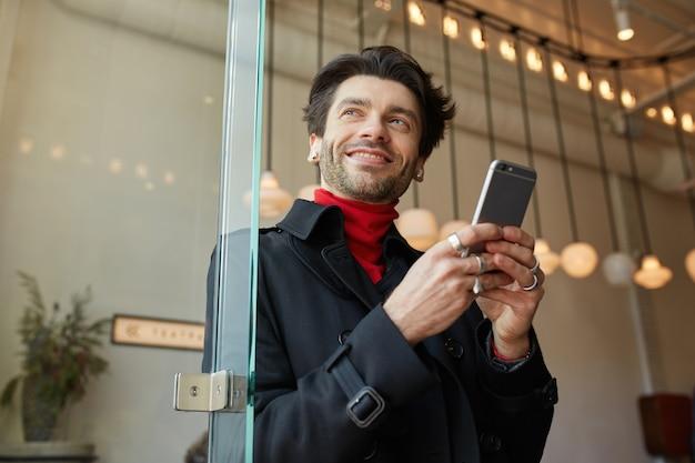 Blij jonge knappe bruinharige met oortelefoons die smartphone houden en vrolijk opzij kijken met een brede glimlach, staande over de achtergrond van het stadscafé