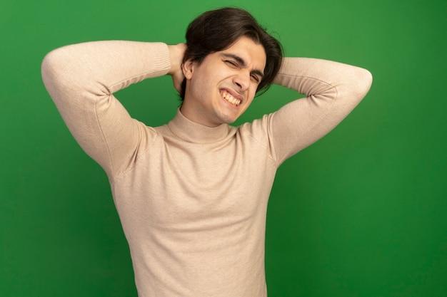 Blij jonge knappe kerel handen op achter hoofd geïsoleerd op groene muur zetten