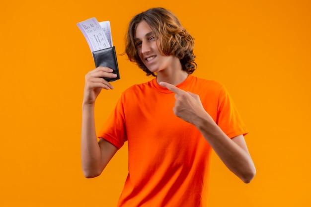 Blij jonge knappe kerel in oranje t-shirt met vliegtickets wijzend met de vinger naar hen kijken camera met zelfverzekerde glimlach staande op gele achtergrond