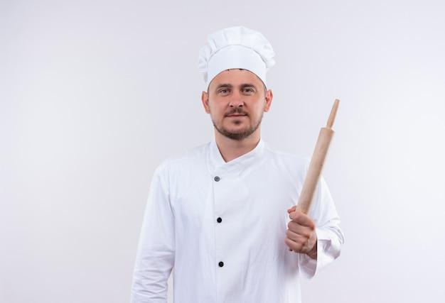 Blij jonge knappe kok in de deegrol van de chef-kok eenvormige holding die op witte ruimte wordt geïsoleerd